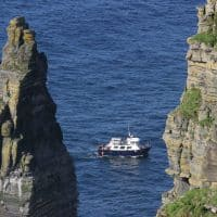 boats cruise under the famous cliffs of moher